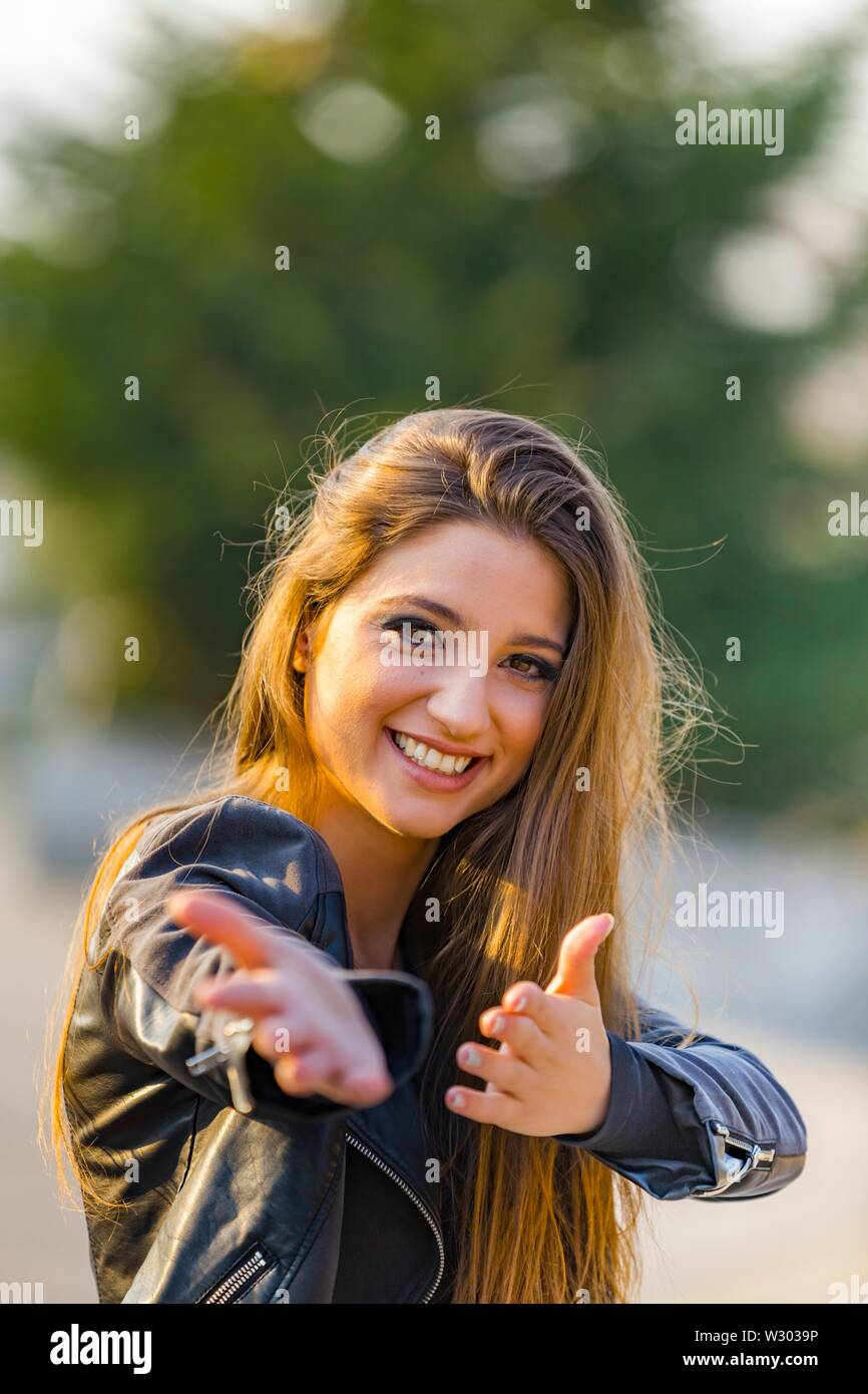 Attractive female portrait looking at camera happy smiling hands offer offering herself doing pantomime - Stock Image