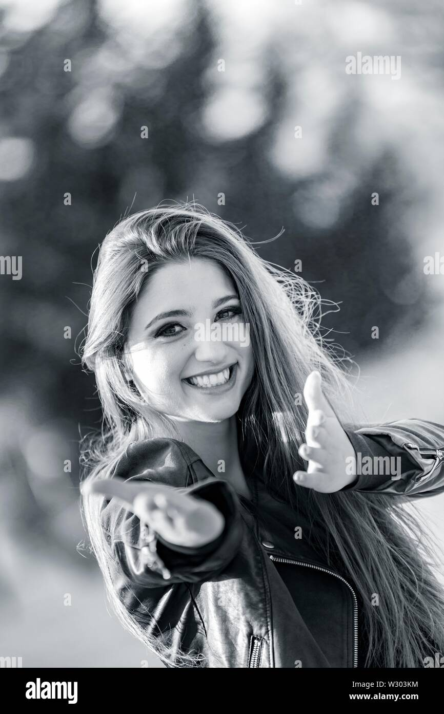 Attractive female portrait looking at camera very happy smiling hands doing pantomime offer offering herself give giving - Stock Image