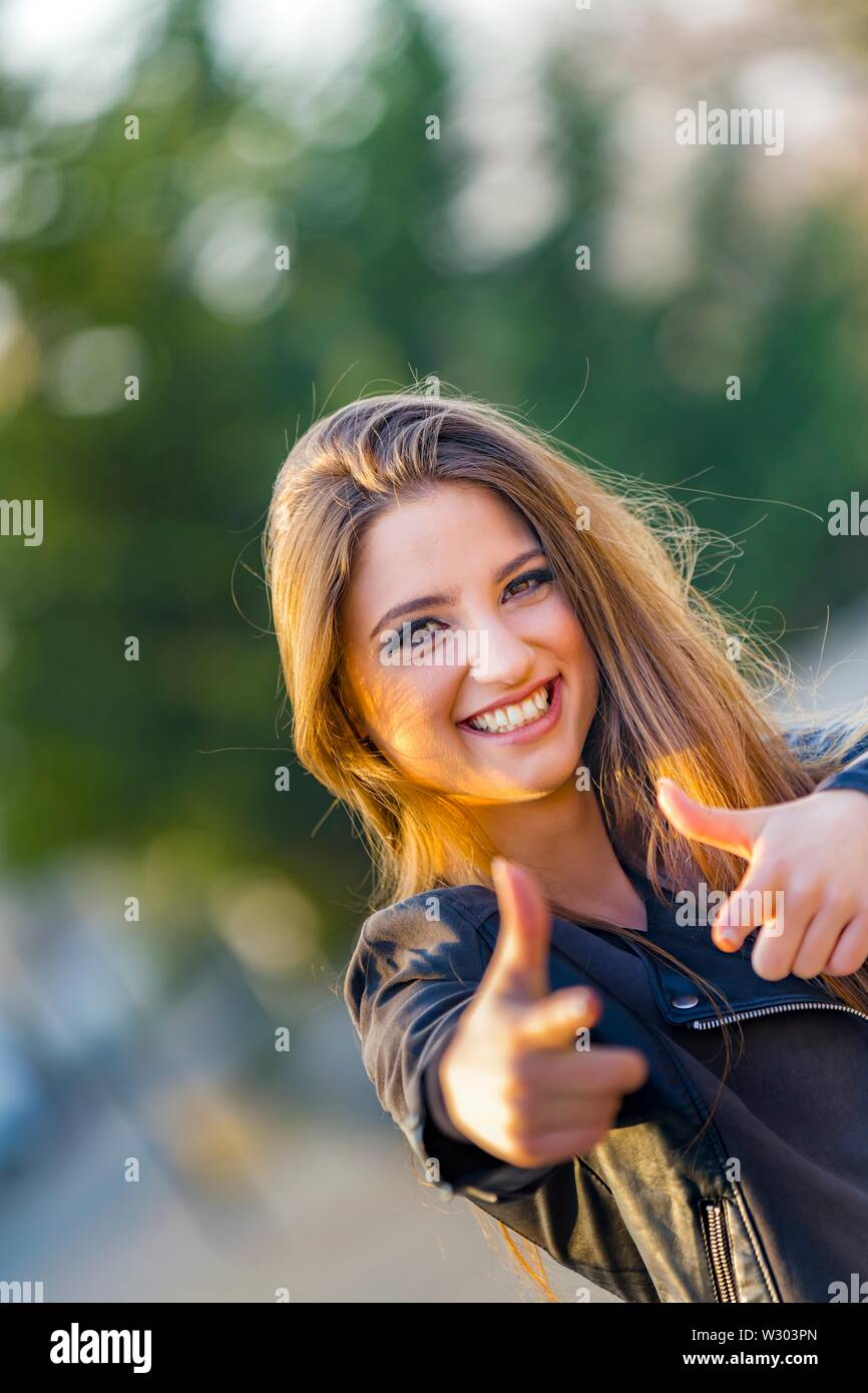 Attractive female portrait looking at camera very happy smiling hands both thumbs up doing pantomime acting dangerous shot hand weapon - Stock Image