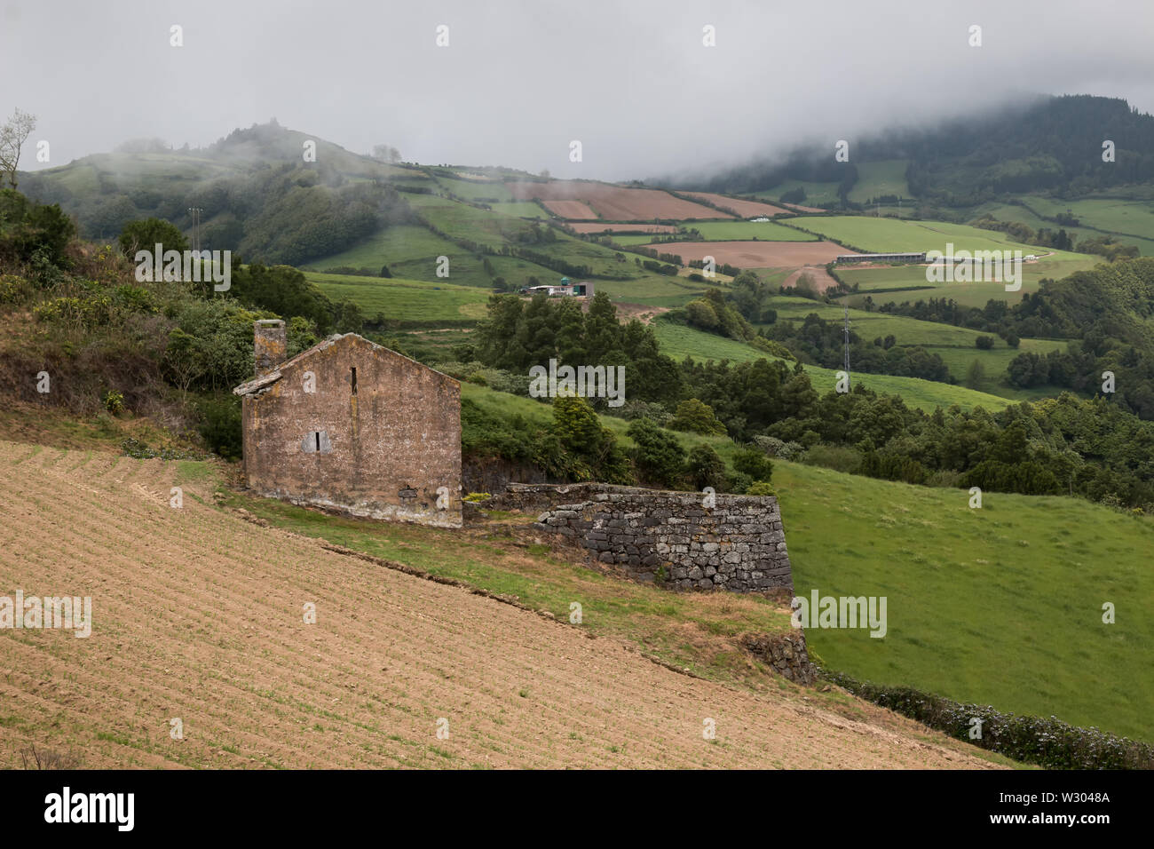 Old abandoned house in the middle of fields and meadows, in a mountain valley. Intense clouds on the sky. South of Sao Miguel, Azores Islands, Portuga - Stock Image