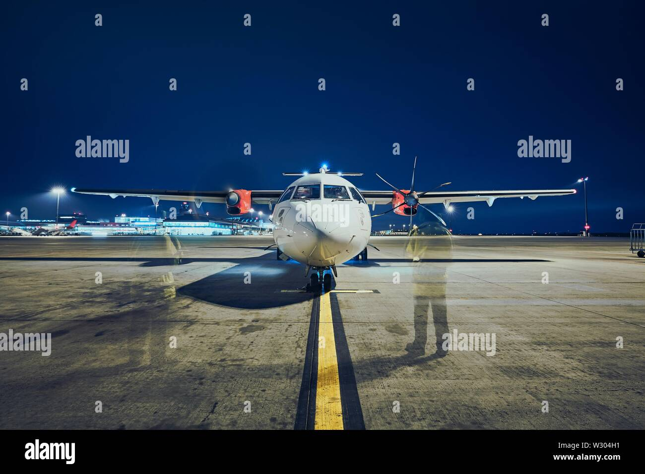 Starting of engines of turboprop airplane before take off against airport at night (long exposure). - Stock Image