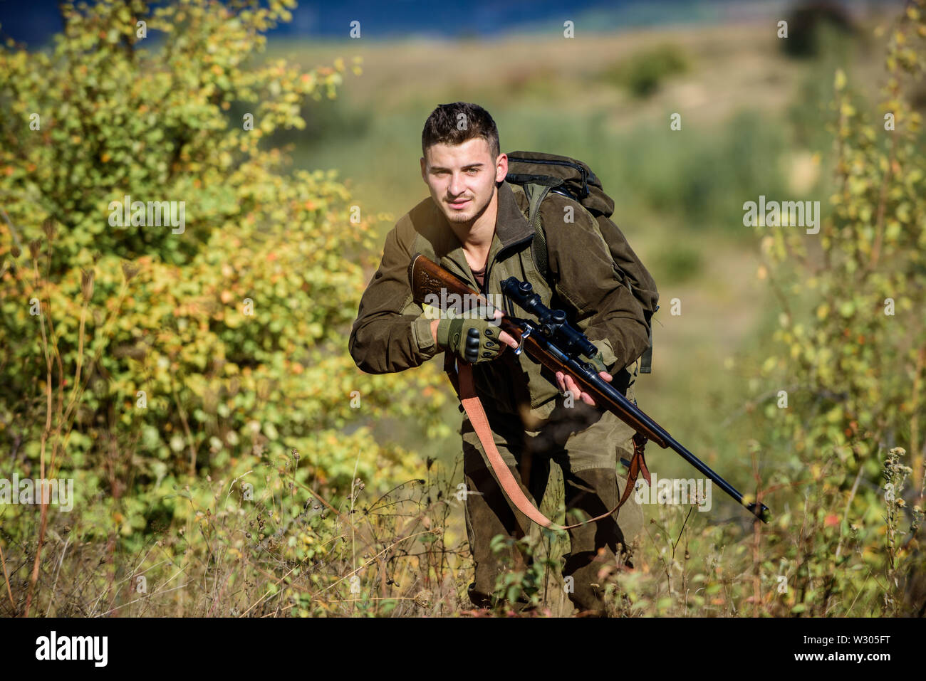 Bearded serious hunter spend leisure hunting. Hunter hold rifle. Man wear camouflage clothes nature background. Hunting permit. Hunting equipment for professionals. Hunting is brutal masculine hobby. - Stock Image