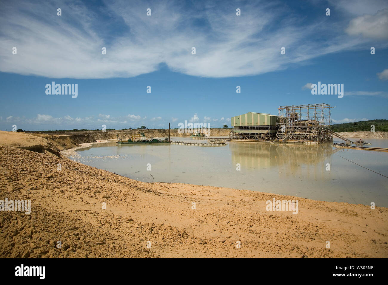 Managing & transporting of titanium mineral sands at mine site.  Mining by dredging in freshwater pond. Dredges pump sand into wet concentrator plant. Stock Photo