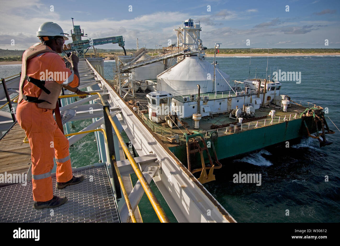 Mining, managing & transporting of titanium mineral sands. Port operations with barge loading & marine jetty work before transhipping product to OGV. Stock Photo