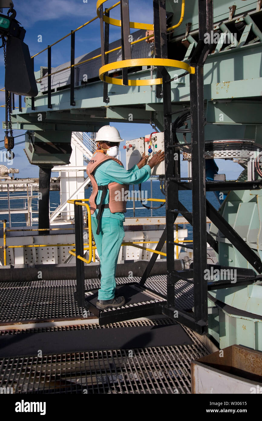 Mining, managing & transporting of titanium mineral sands. Port floating marine jetty with operator at control panel of boom during barge loading. Stock Photo