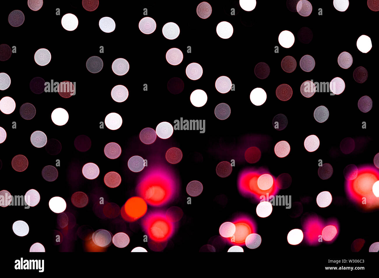 Unfocused abstract colourful bokeh on black background. defocused and blurred many round light. - Stock Image