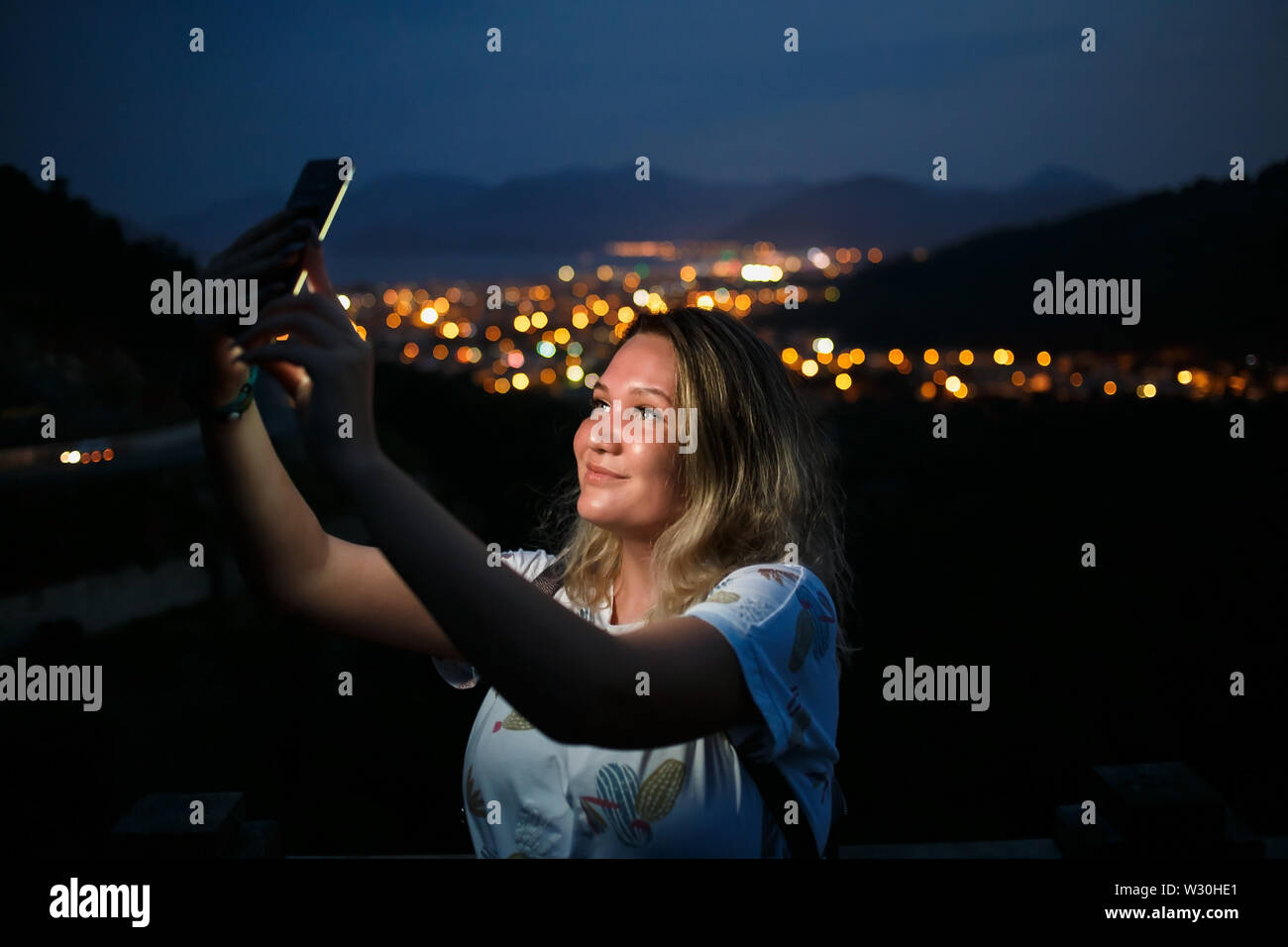 Young woman taking selfie on top of the hill observing the night city view. Good light from screen. - Stock Image