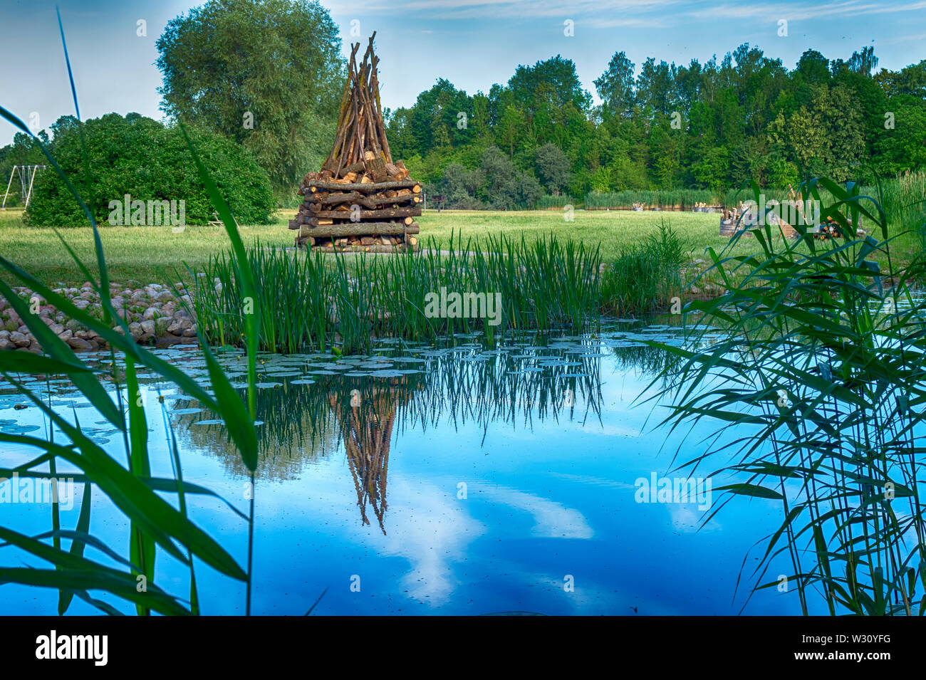 Tranquil lake with large ready built bonfire on the further shore waiting to be lit in the evening for a celebration or party - Stock Image