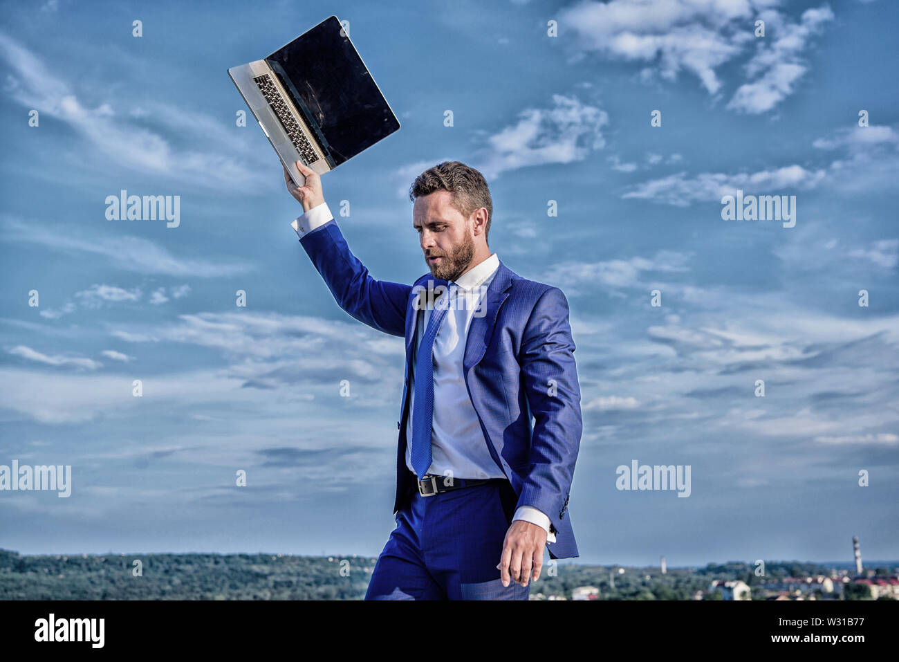 Looking for wifi network. Businessman suit outdoors sky background. Man raise up hand with laptop. Lack of coverage. Businessman with laptop wait while connect with internet. Connection problems. - Stock Image