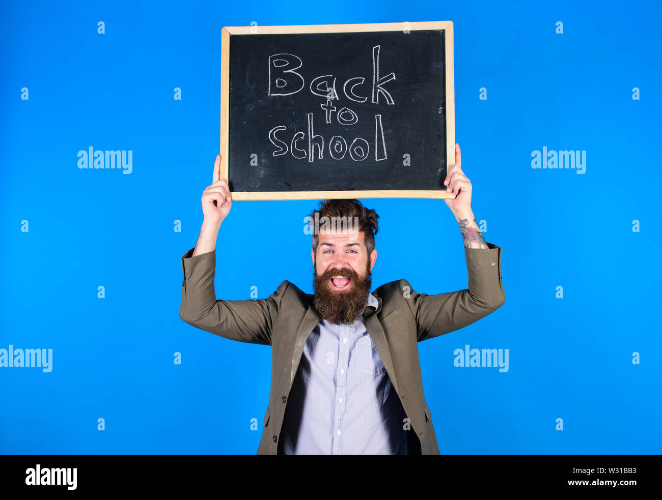 Teacher bearded man holds blackboard with inscription back to school blue background. Teaching stressful occupation. Do not be upset. Teacher with tousled hair stressful about school year beginning. - Stock Image