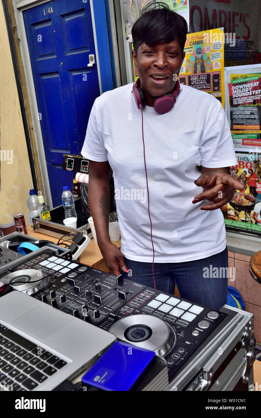 Black female DJ setting up music outside shop window on two mixing decks at Bristol St Paul's carnival festival Stock Photo