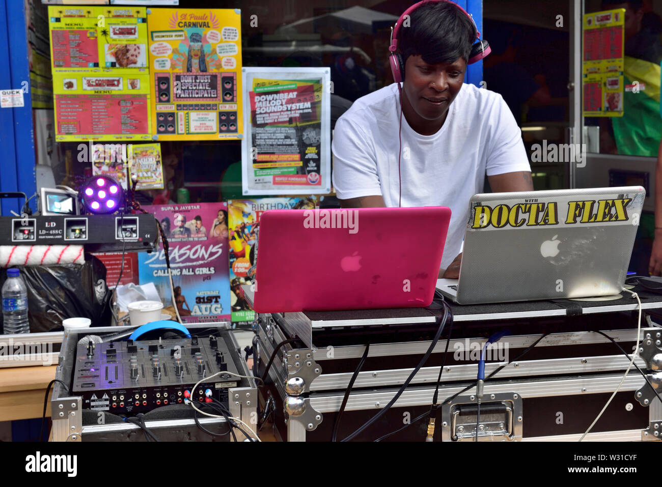 Black female DJ setting up music outside shop window on two mixing decks at Bristol St Paul's carnival festival - Stock Image