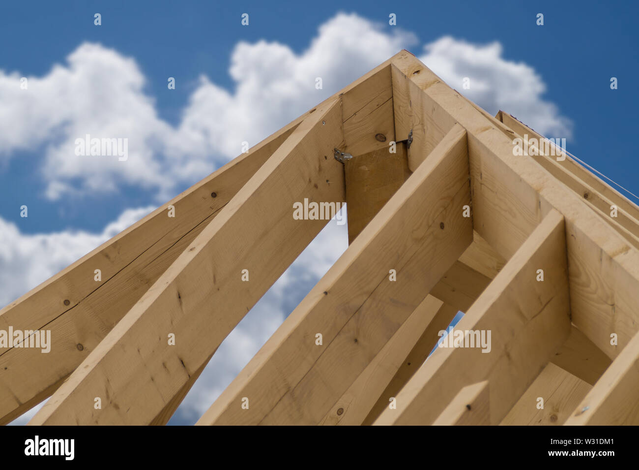 Wooden roof construction of a new residential house. Close up against blue cloudy sky. Construction site. - Stock Image