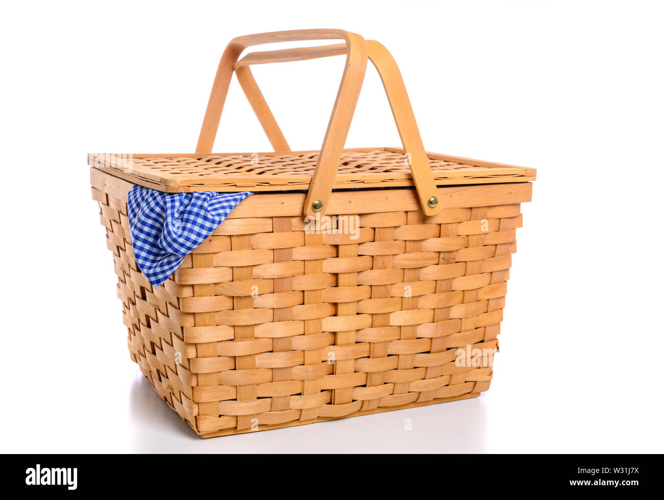 A brown wicker picnic basket on a white background with gingham cloth Stock Photo