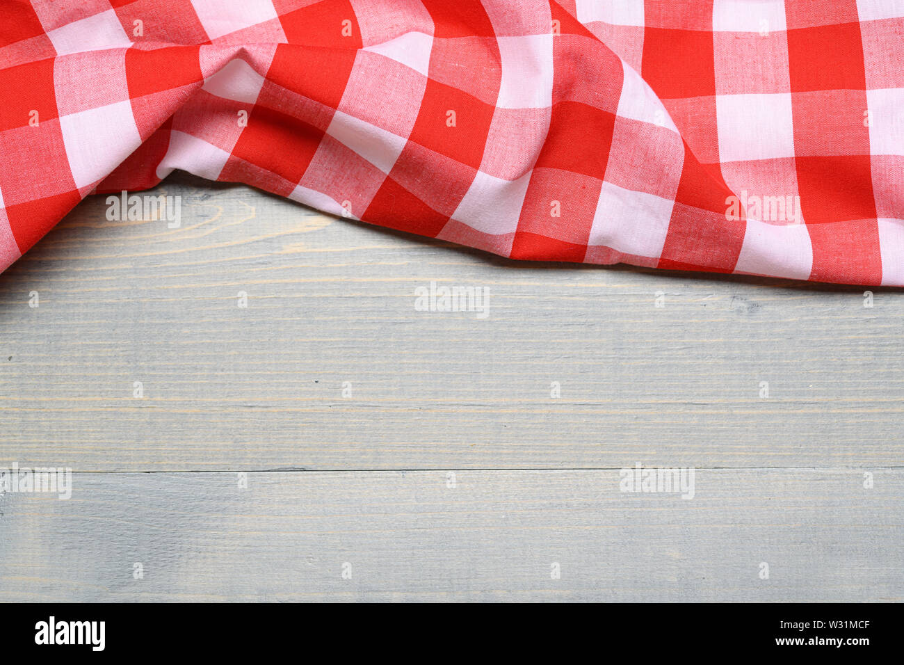 a checked gingham picnic tablecloth on old wooden table top view Stock Photo