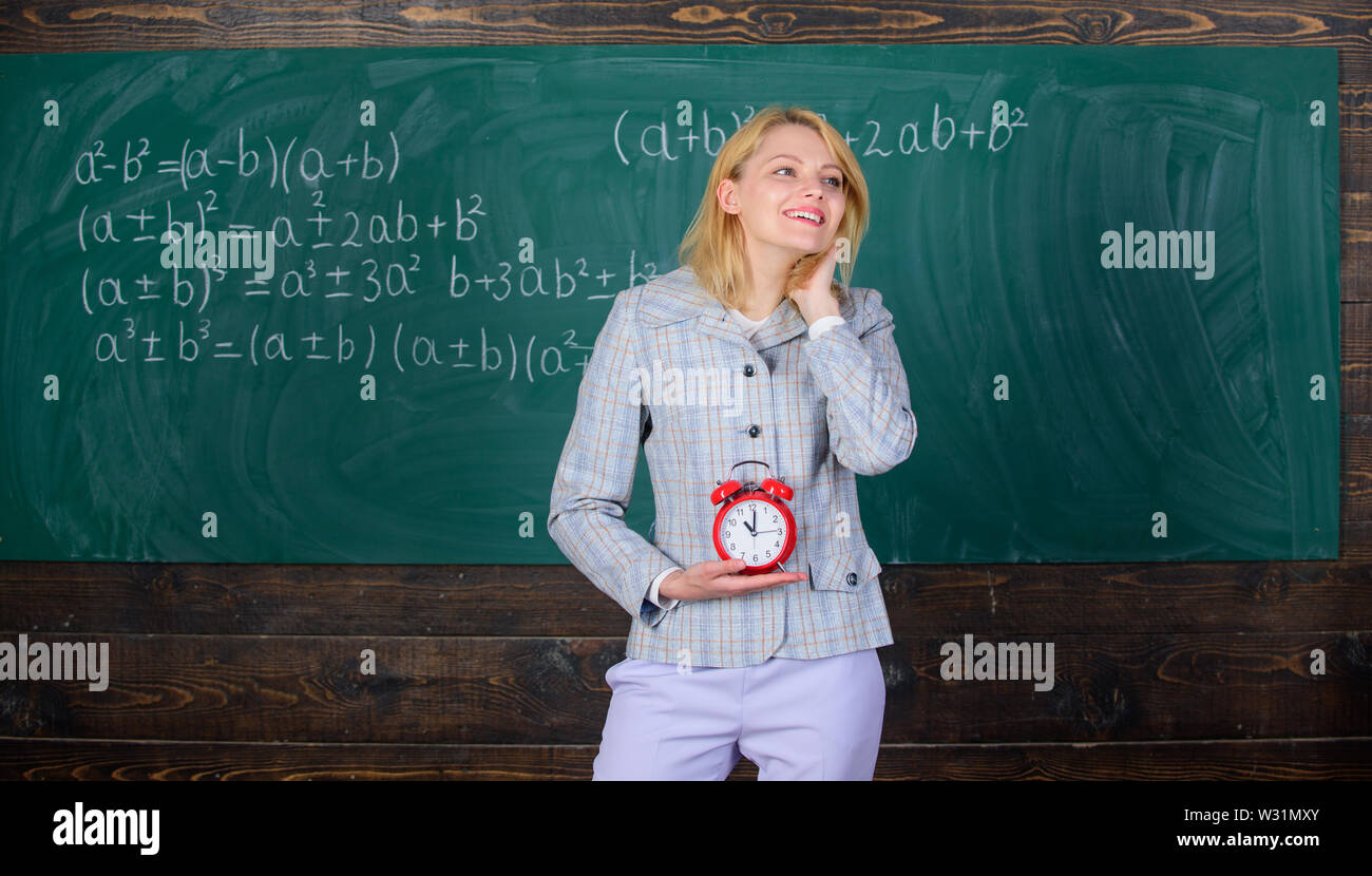 Lessons schedule. Welcome teacher school year. Experienced educator start lesson. She cares about discipline. Woman teacher hold alarm clock. Girl formal wear school lecturer. What time is it. - Stock Image