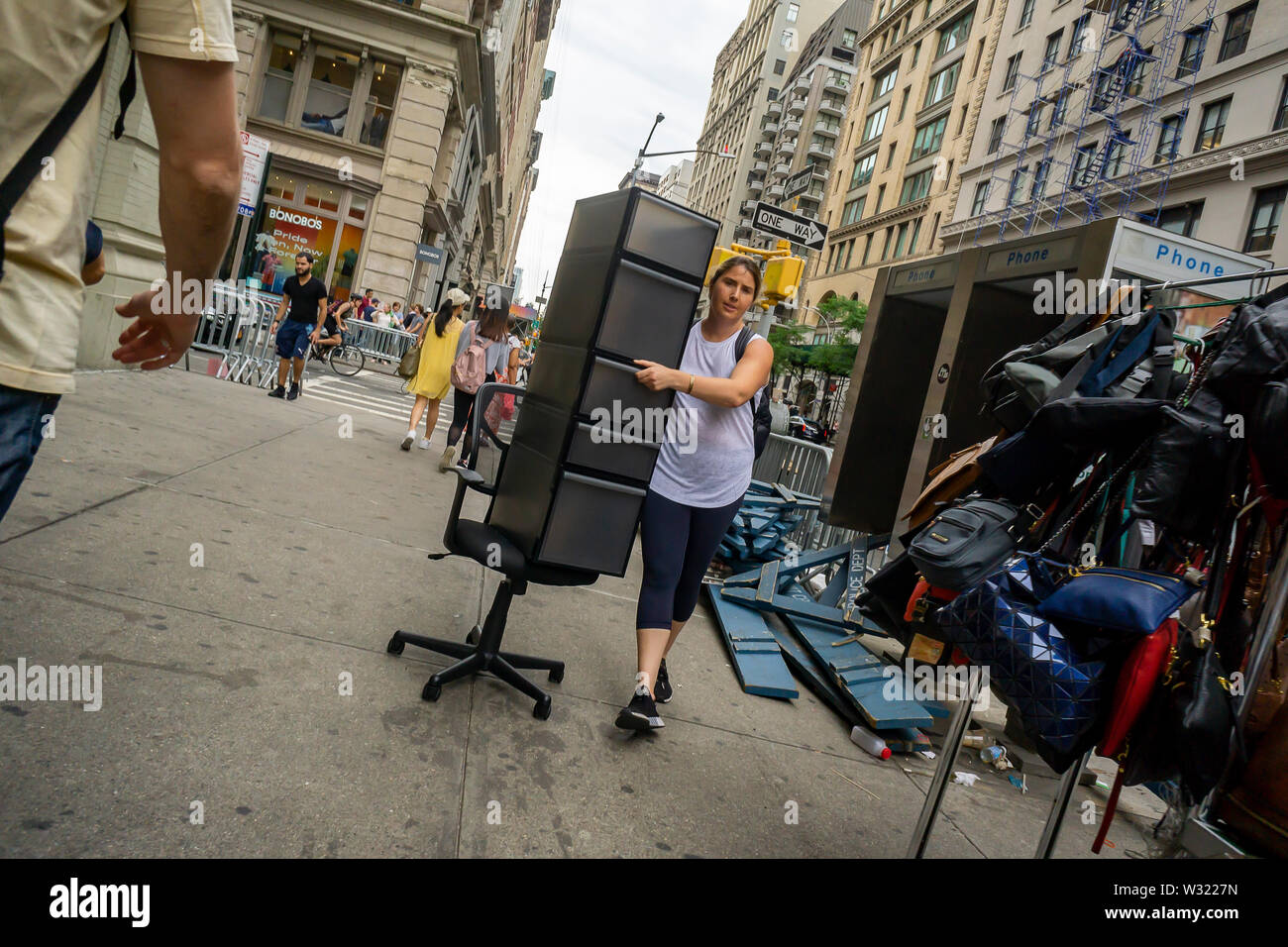 A woman schleps a storage unit on an office chair as a makeshift dolly in the Flatiron neighborhood of New York on Tuesday, July 2, 2019. (© Richard B. Levine) - Stock Image