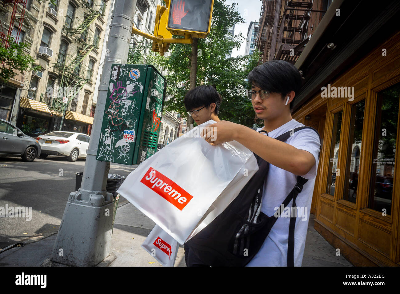 "Shoppers with their Supreme ""merch"" outside the Supreme store on the Bowery in New York on Friday, July 5, 2019. (© Richard B. Levine) - Stock Image"