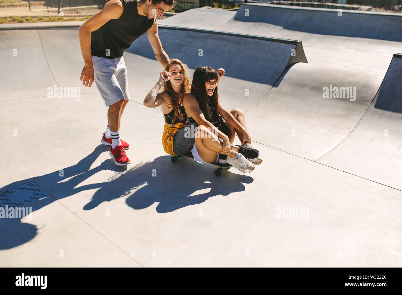 Group of friends having fun at skate park. Young man and two girls playing with a skateboard at skate park. Stock Photo