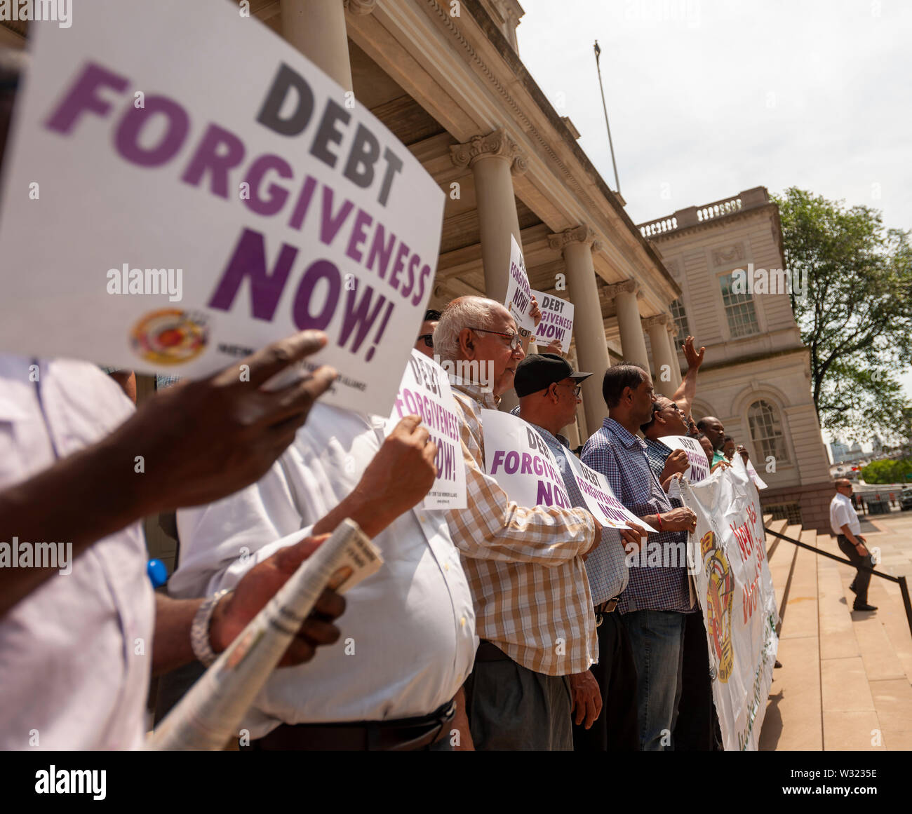 New York taxi drivers and their supporters rally on the steps of NY City Hall in Thursday, July 11, 2019 for a news conference calling for debt forgiveness for their medallion loans. Medallion brokers allegedly took advantage of drivers who bought medallions at artificially inflated prices and ended up burdened with debt. A number of drivers have filed for bankruptcy or are considering it and there have been a few suicides amongst stressed drivers. (© Richard B. Levine) - Stock Image