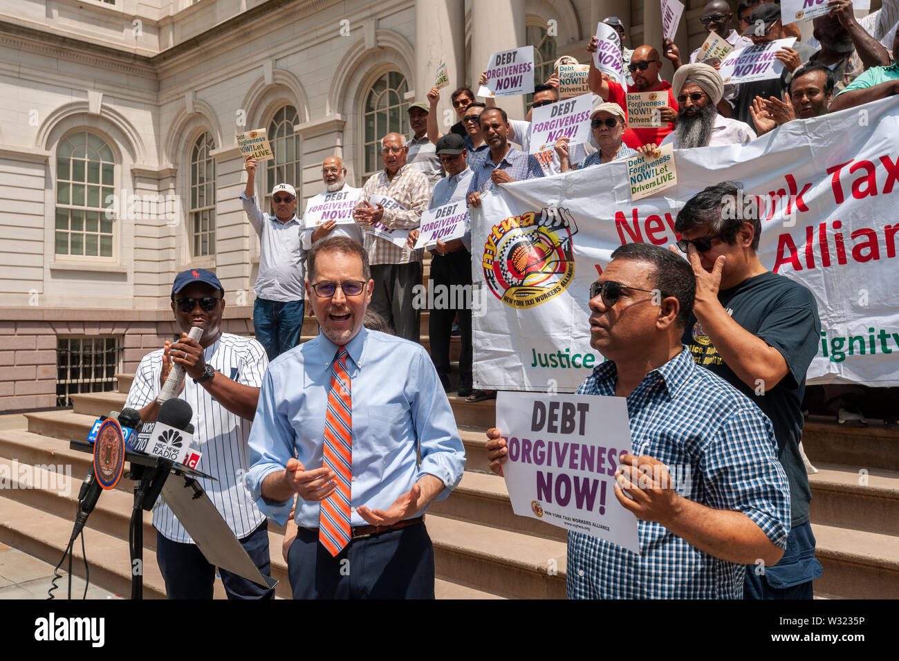 NYC Council Member Mark Levine speaks at a press conference with New York taxi drivers and their supporters on the steps of NY City Hall on Thursday, July 11, 2019  calling for debt forgiveness for their medallion loans. Medallion brokers allegedly took advantage of drivers who bought medallions at artificially inflated prices and ended up burdened with debt. A number of drivers have filed for bankruptcy or are considering it and there have been a few suicides amongst stressed drivers. (© Richard B. Levine) - Stock Image