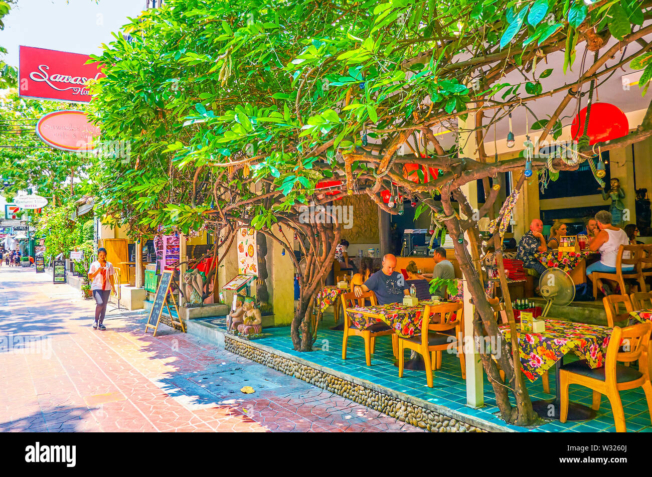 BANGKOK, THAILAND - APRIL 22, 2019: The shaddy terrace of restaurant with twisted tree at the facade, on April 22 in Bangkok - Stock Image