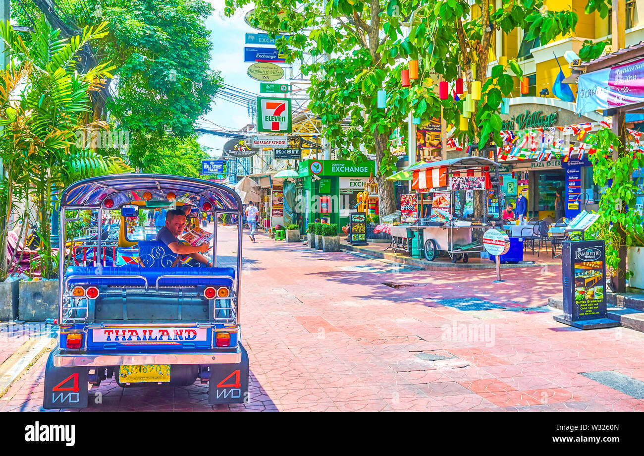 BANGKOK, THAILAND - APRIL 22, 2019: The tuk-tuk driver waits for clients on empty Ram Buttri road, on April 22 in Bangkok - Stock Image