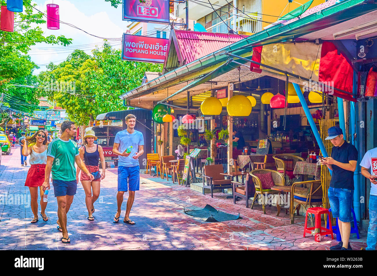 BANGKOK, THAILAND - APRIL 22, 2019: People walk along the bars and restaurants of Ram Buttri street of Banglampu district, on April 22 in Bangkok - Stock Image