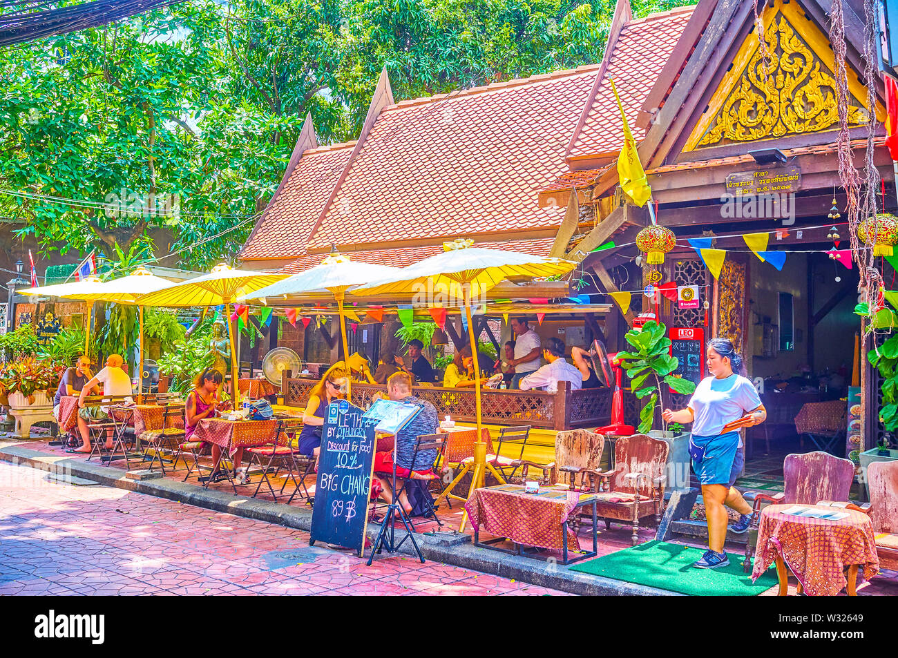 BANGKOK, THAILAND - APRIL 22, 2019: The cozy open air terrace of the restaurant, located in traditional Thai building with carved entrance porch, on A - Stock Image