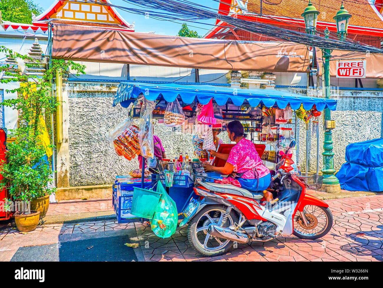 BANGKOK, THAILAND - APRIL 22, 2019: The street vendor of beverages makes coffee for the client, sitting at the motorcycle cart in Banglampu district, - Stock Image