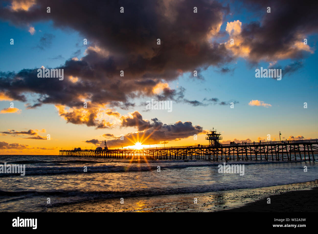 Watching the Sunset through the san clemente pier down at the beach on the sand Stock Photo