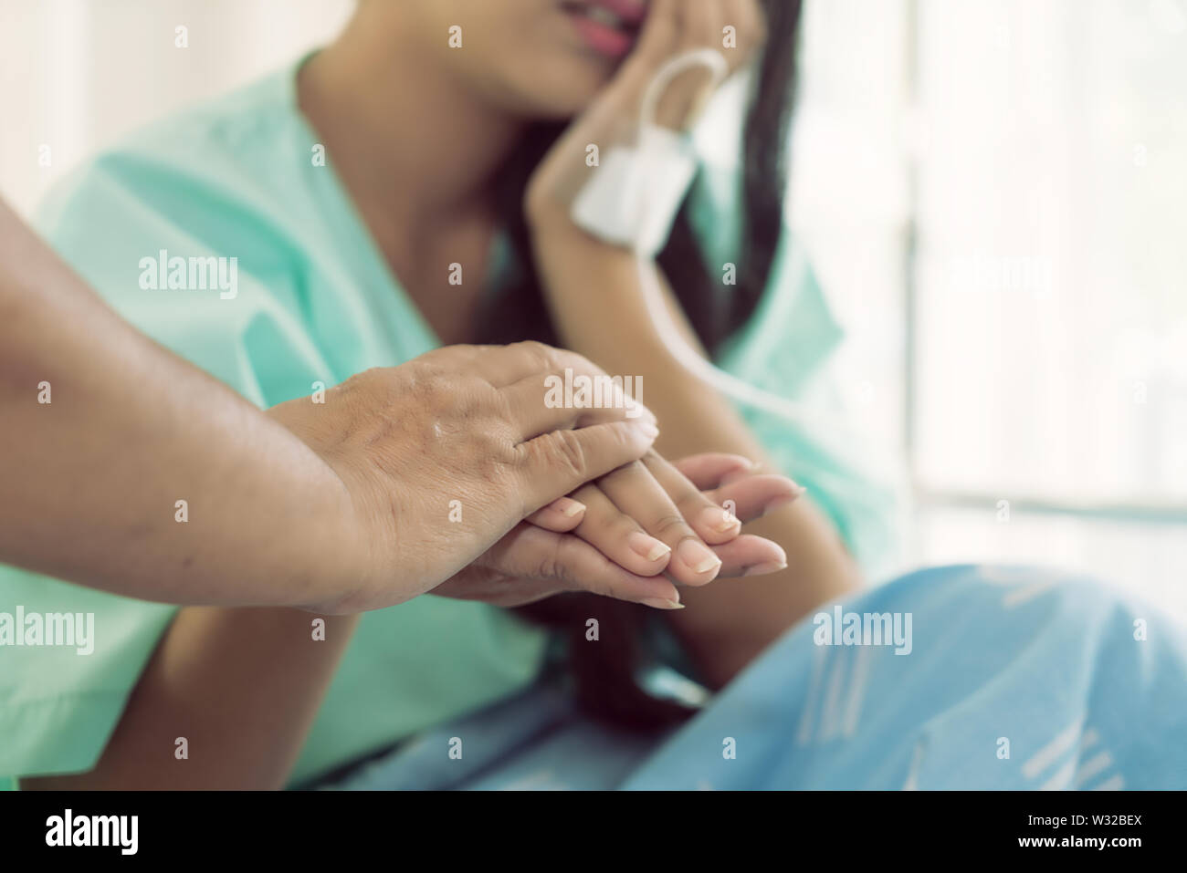 Mother hands holding her daughter patient hand sitting at the desk for encouragement, empathy, cheering and support while medical examination. Bad new - Stock Image