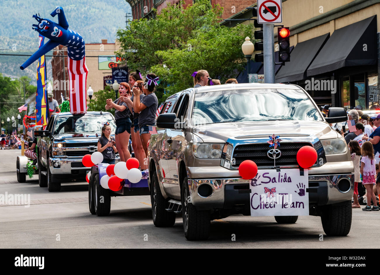 High school cheerleaders ride float in annual Fourth of July Parade; small mountain town of Salida; Colorado; USA - Stock Image