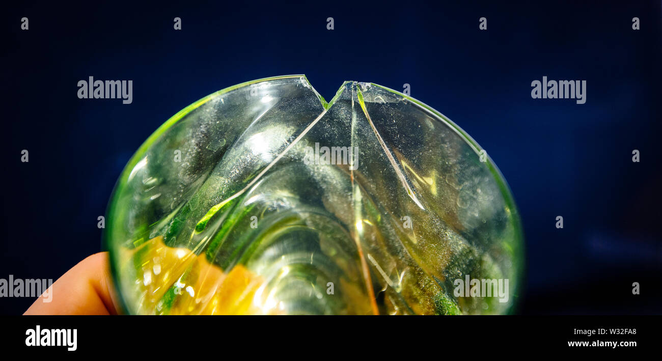 Man hand holding broken glass isolated light back background - close-up above view - Stock Image