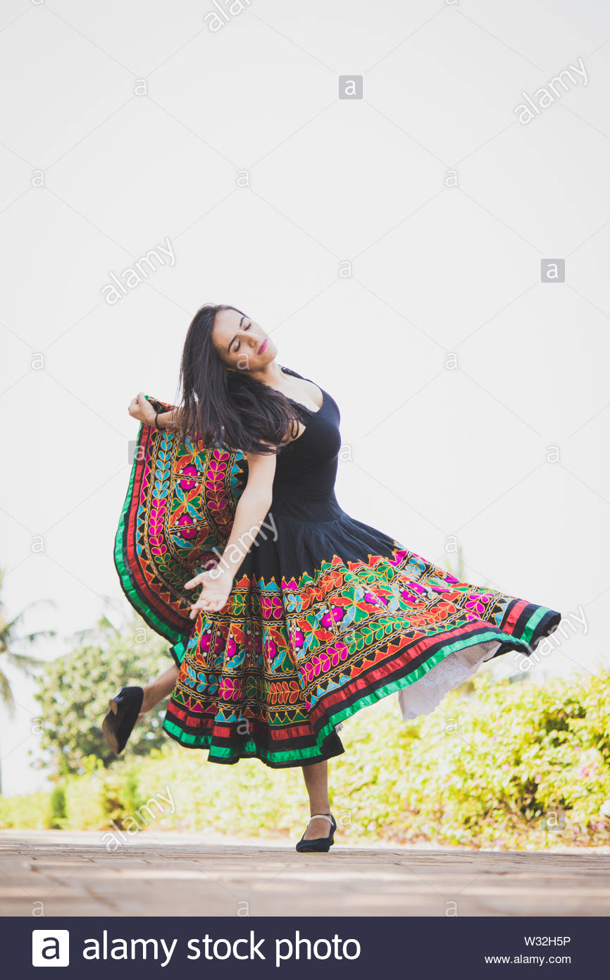 Young woman dancing outdoors in colorful dress - Stock Image