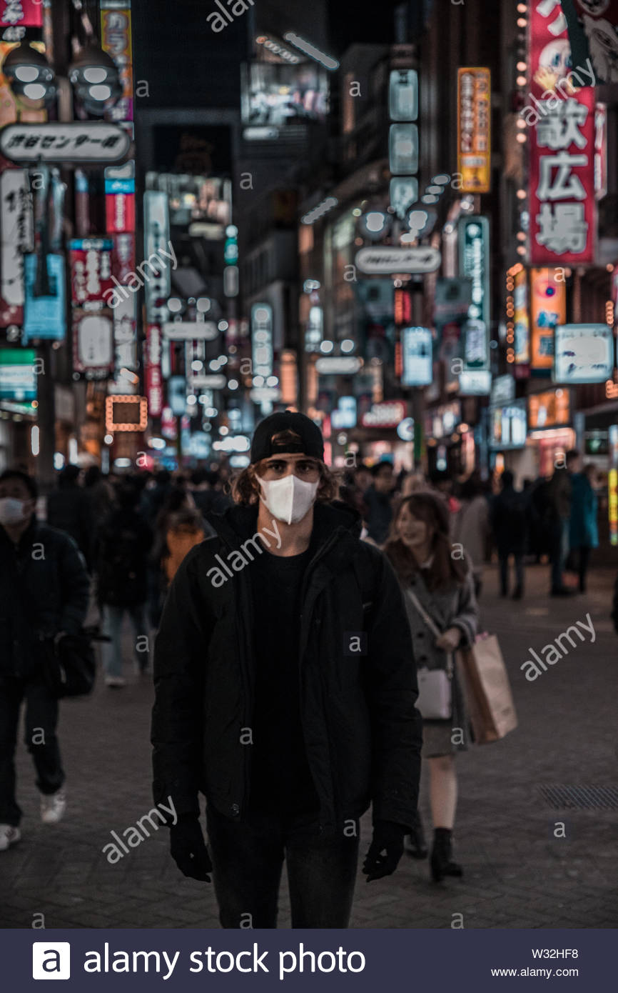 Man wearing safety mask standing on crowded street - Stock Image