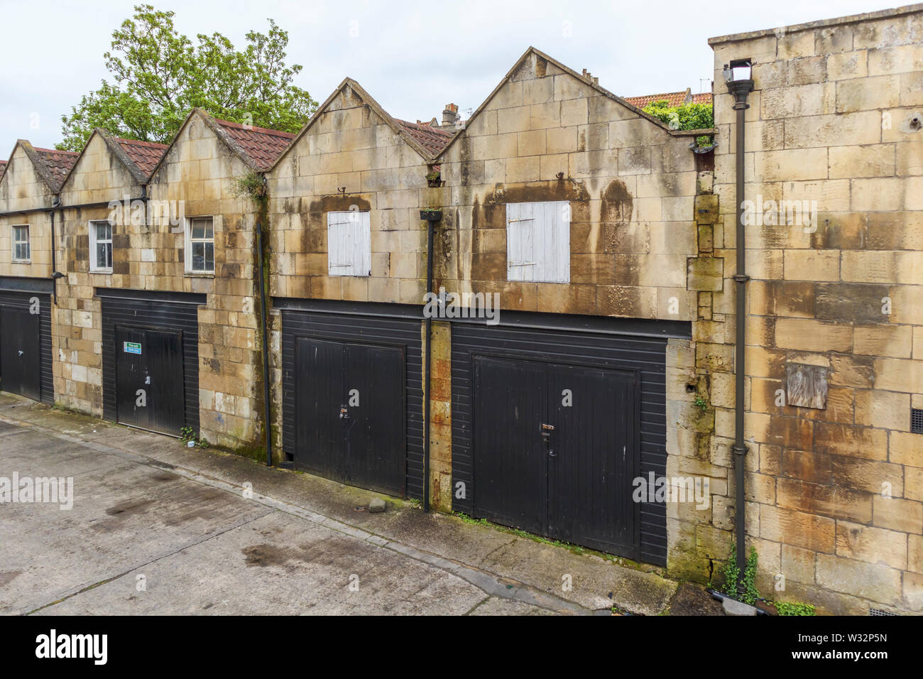 Row of historic gabled stable buildings now used as lock-up garages in Bath, the largest city in Somerset, south-west England, UK - Stock Image