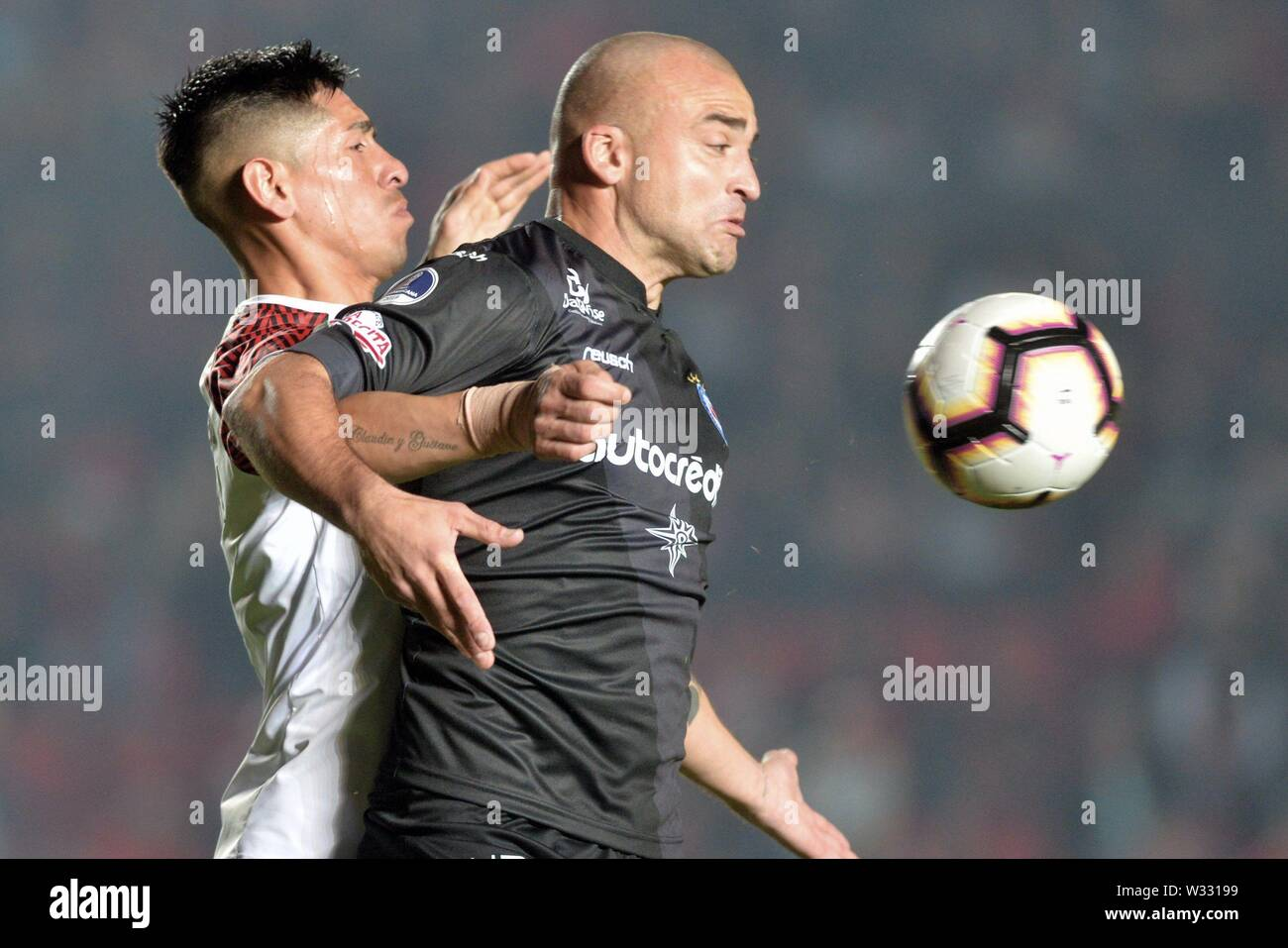 Santa Fe, Argentina. 12th July, 2019. Colon's Emanuel Olivera (L) vies for the ball with Santiago Silva (R) of Argentinos Juniors during the Copa Sudamericana round of 16 first leg match between Club Atletico Colon and Asociacion Atletica Argentinos Juniors at the Brigadier General Estanislao Lopez stadium in Santa Fe, Argentina, 11 July 2019. Credit: JAVIER ESCOBAR/EFE/Alamy Live News - Stock Image