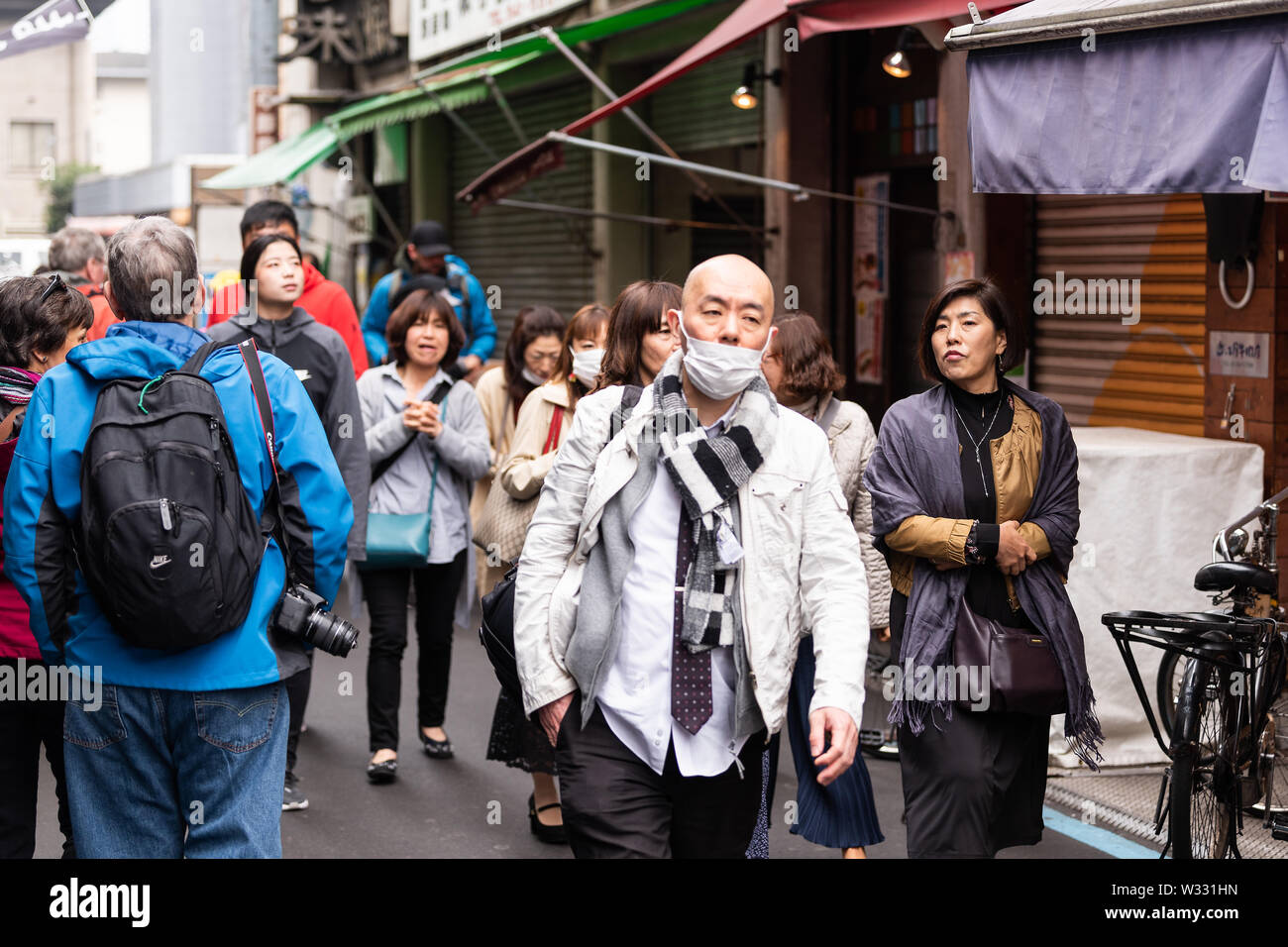 Tokyo, Japan - March 30, 2019: Chinese and Asian tourists, people walking on road street or alley by market by food vendors in Tsukiji outer fish mark - Stock Image