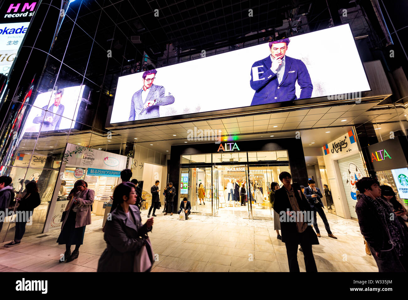 Shinjuku, Japan - April 4, 2019: Street outside view on entrance to Studio Alta shopping mall with stores, shops and people walking on sidewalk at nig - Stock Image