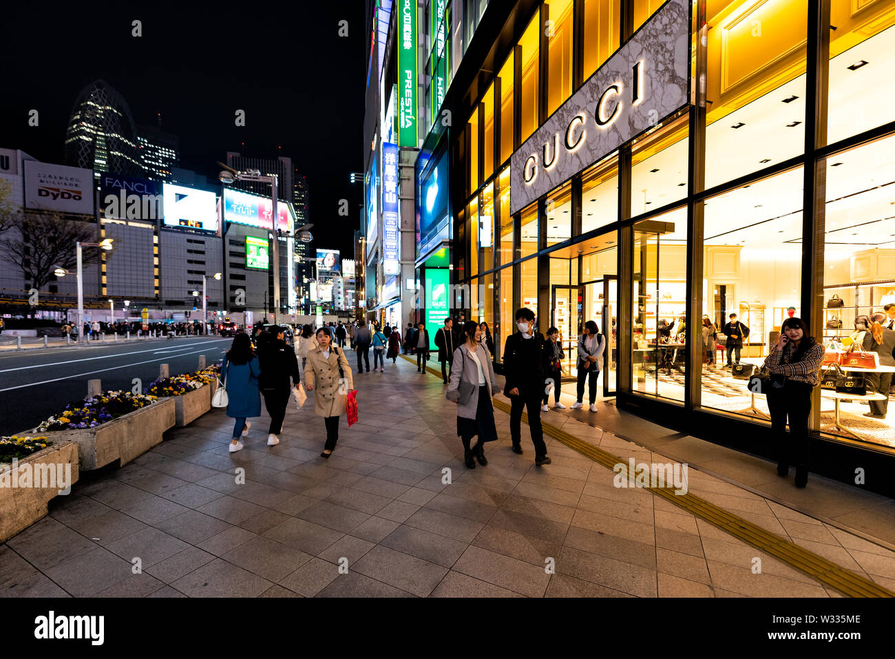 Shinjuku, Japan - April 4, 2019: Street outside view on entrance to Gucci luxury italian store shop at M Square by sidewalk with people walking at nig - Stock Image