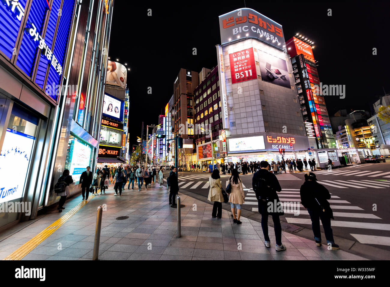 Shinjuku, Japan - April 4, 2019: Street outside view on Bic Camera electronics store shop at M Square with people crossing scramble crosswalk at night - Stock Image