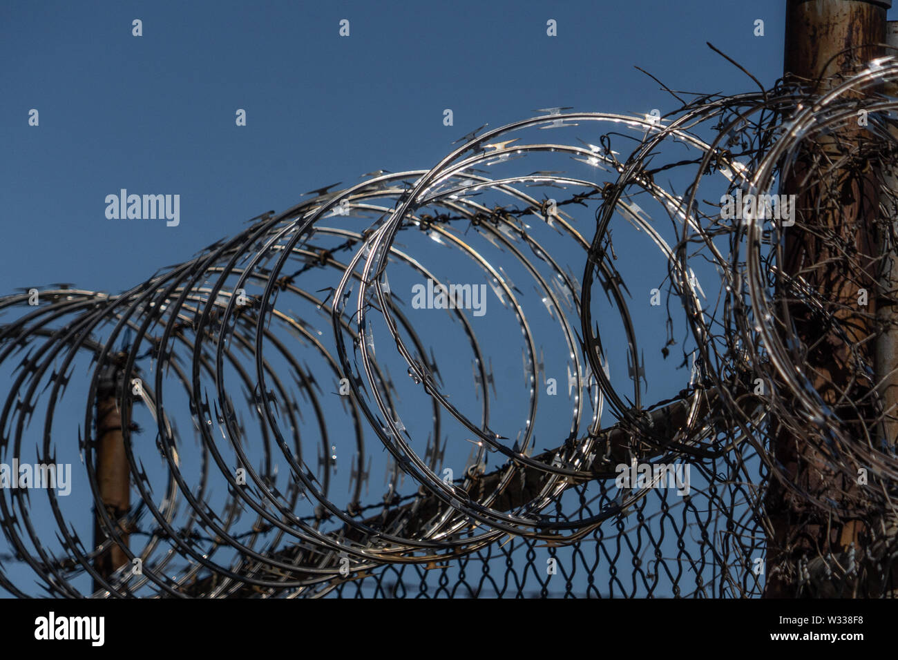 barbed wire on a fense with a blue sky behind - Stock Image