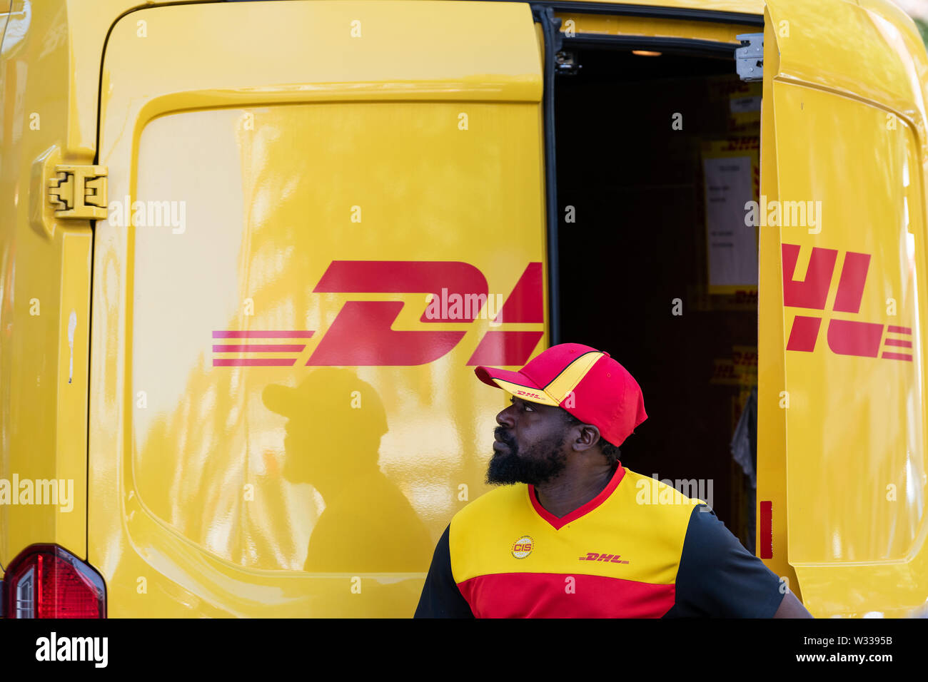 London, UK - September 13, 2018: Closeup of DHL delivery truck in Chelsea area of city with man opening back door on street outside - Stock Image