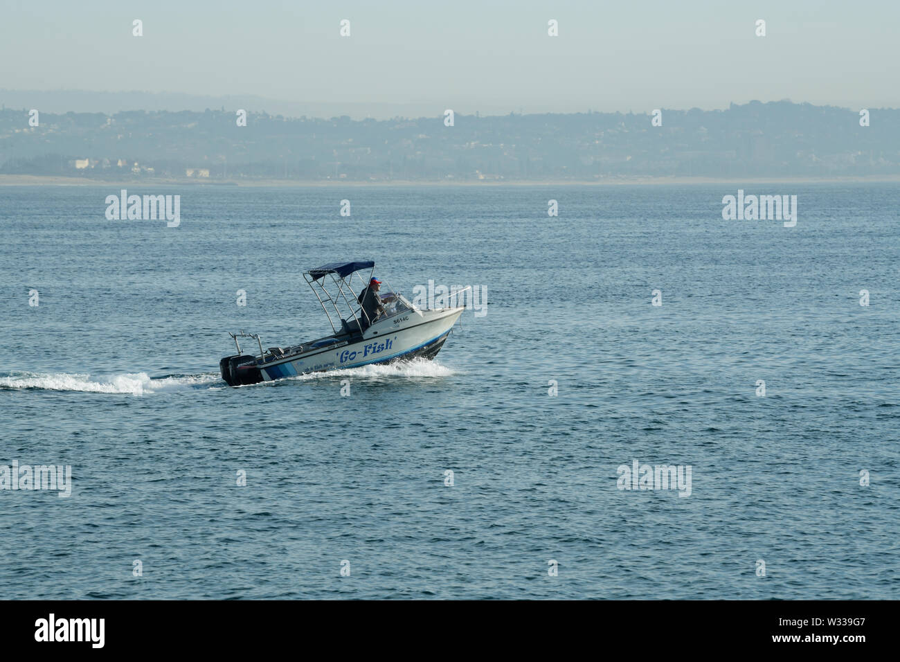 Durban, KwaZulu-Natal, South Africa, two adult men in motorboat cruising into ocean for deep sea fishing, landscape, people, movement, sport, activity - Stock Image