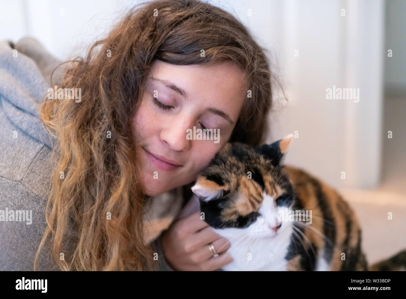 Closeup portrait of happy smiling young woman bonding with calico cat pet companion, bumping rubbing bunting heads, friends showing affection - Stock Image