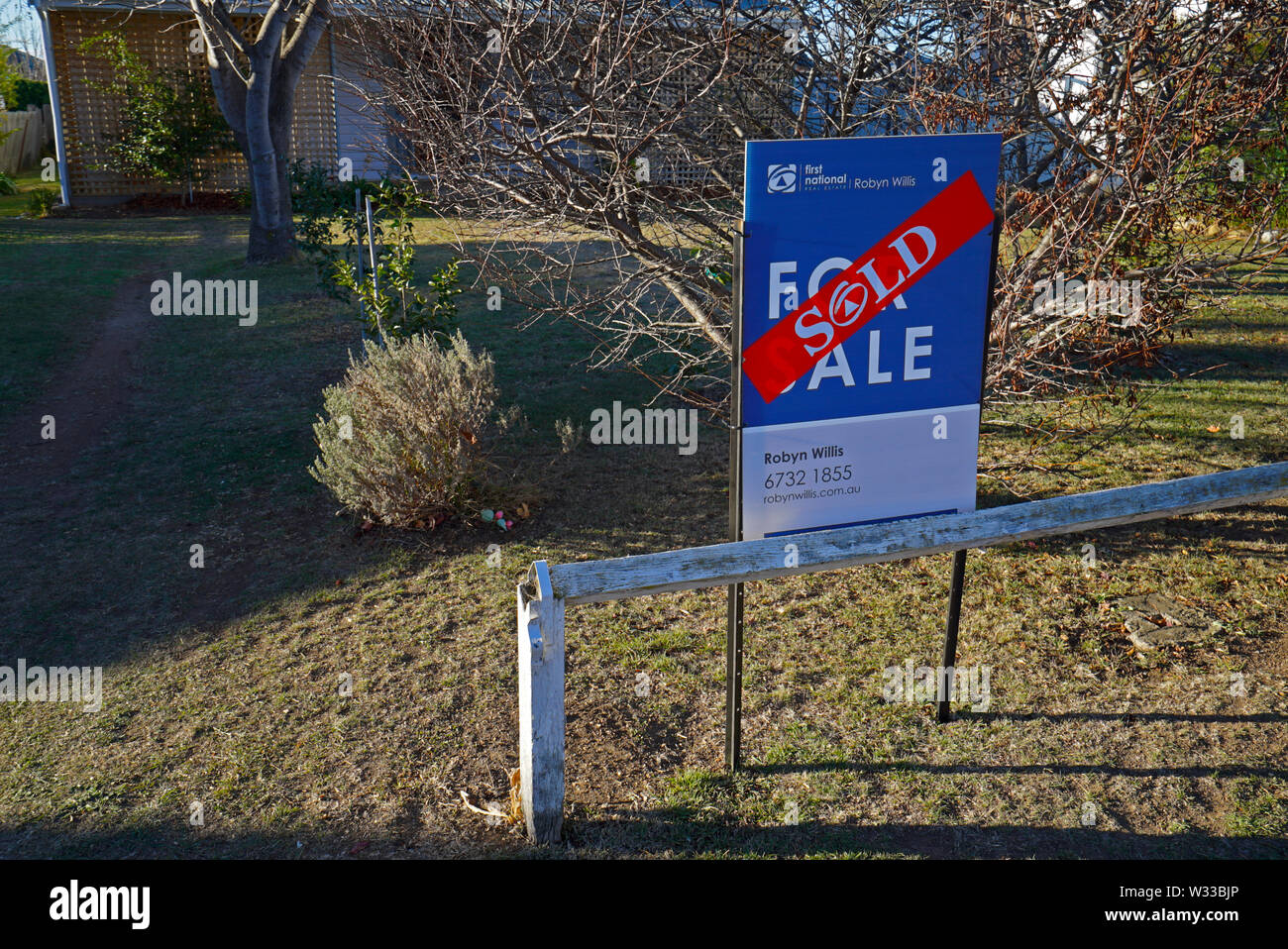 sold sticker across a sold sign outside a house in the northern new south wales town of Glen Innes, australia Stock Photo