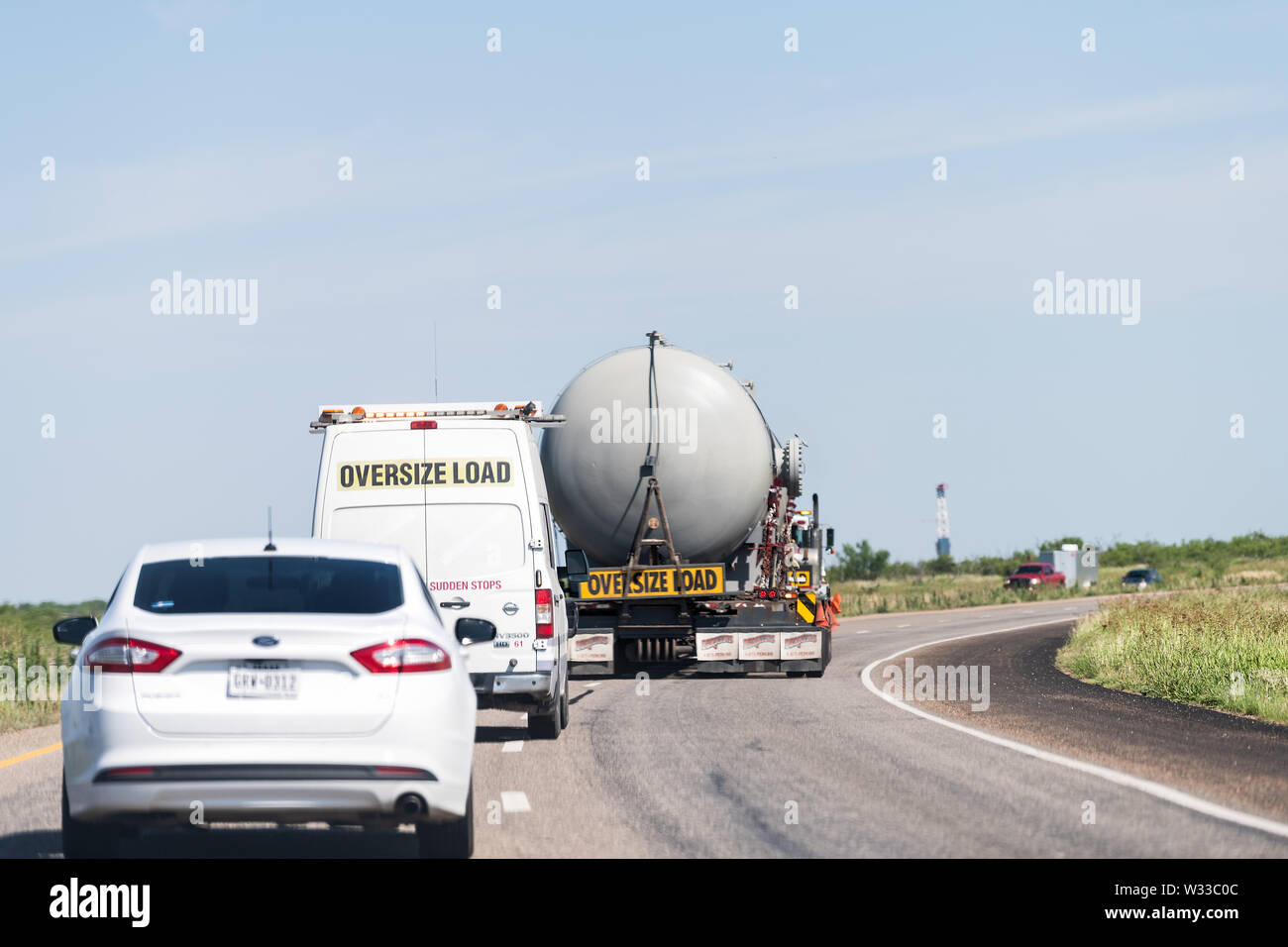 Post, USA - June 8, 2019: Highway road 84 in Texas countryside with oversize load truck blocking traffic Stock Photo