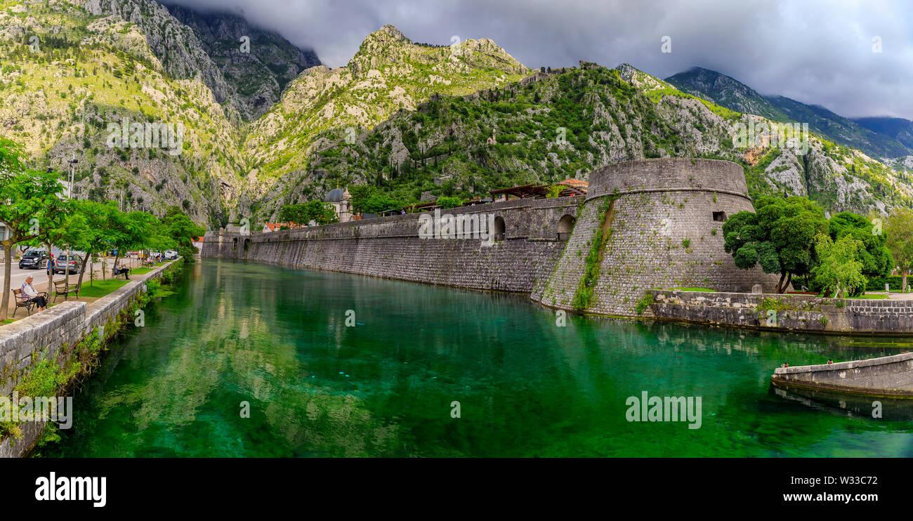 Kotor, Montenegro - May 30, 2019: Panorama of Kotor Bay or Boka Kotorska emerald water, mountains, ancient stone city wall of former Venetian fortress - Stock Image