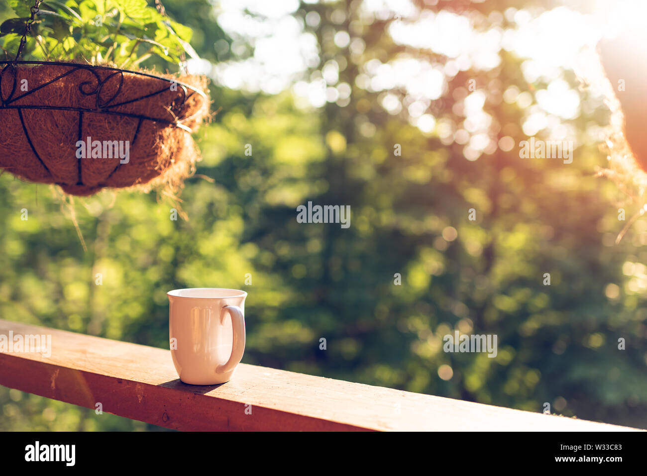 Hanging potted plant with bokeh background on porch of house with sunrise sun and coffee mug on wooden cabin cottage - Stock Image